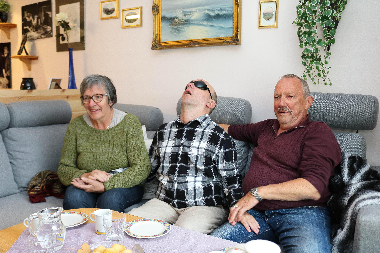 Døvblind mann sammen med sine foreldre i en sofa, far til høyre og mor til venstre.