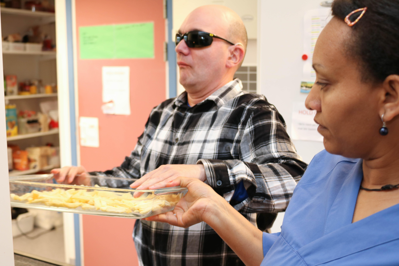 Kvinne hjelper døvblind mann med å løfte en ildfast form med frossen pomfritt.