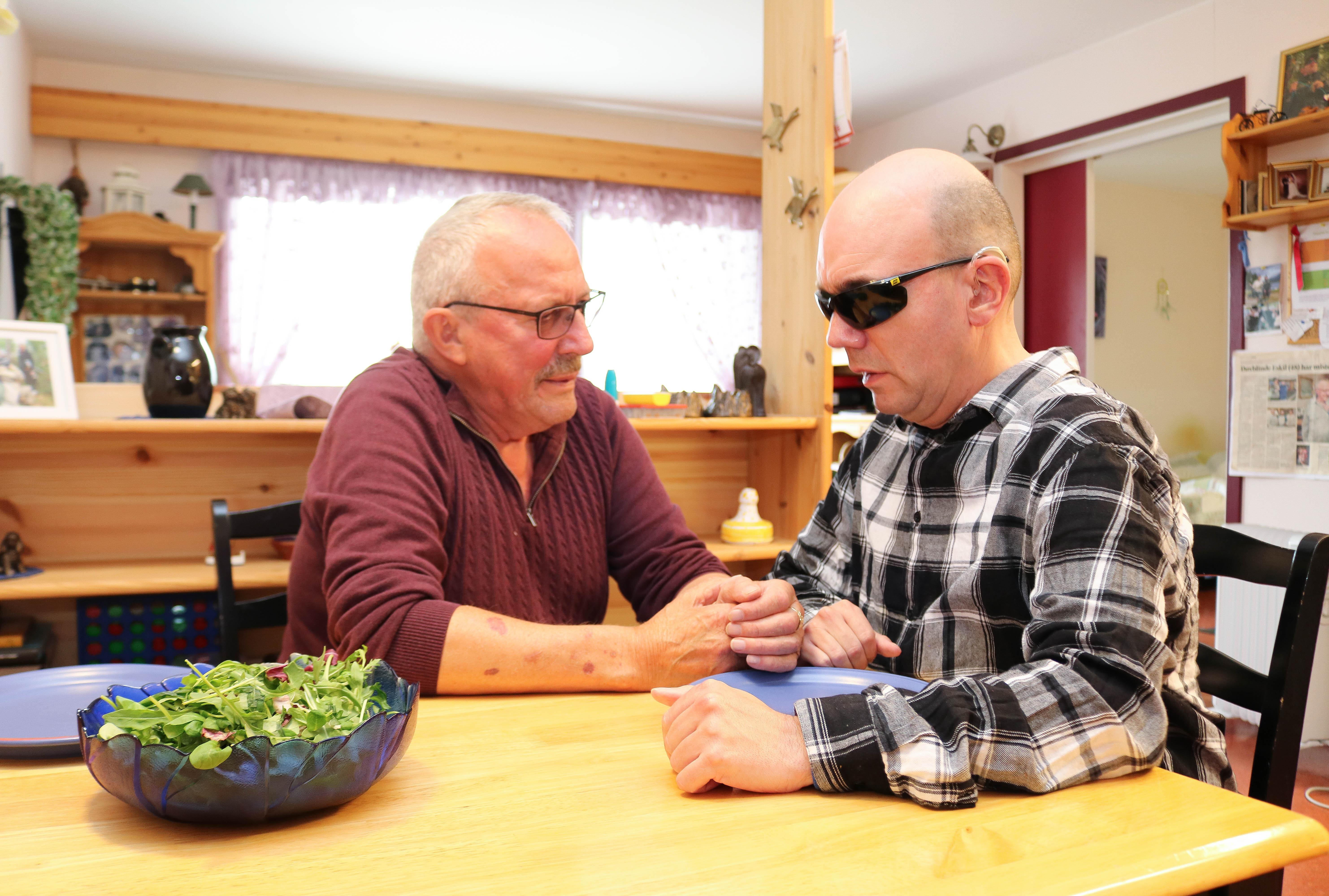 Døvblind mann sitter ved kjøkkenbordet sammen med sin far, de venter på middag.