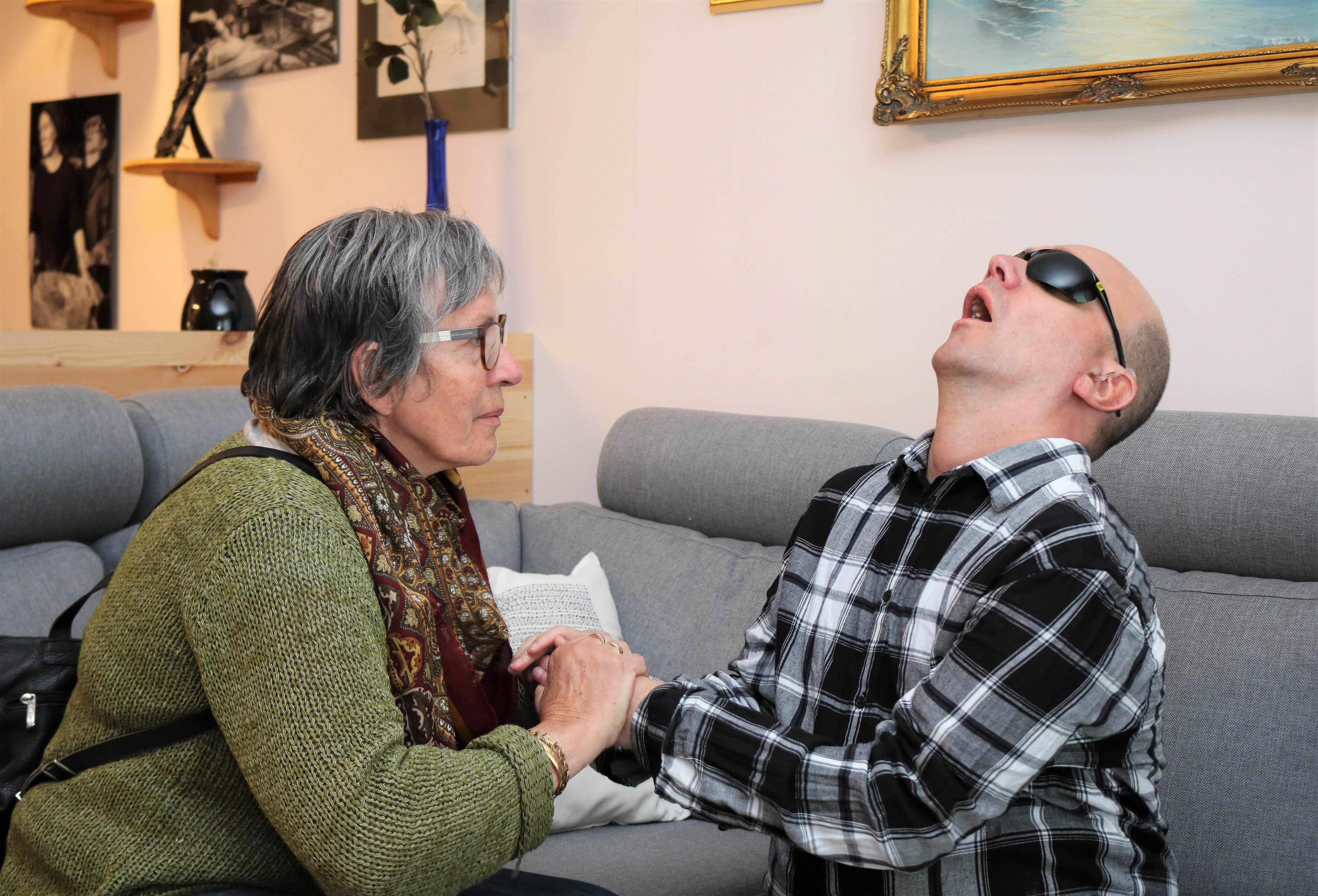 Kvinne kommuniserer med sin sønn gjennom taktilt tegnspråk.