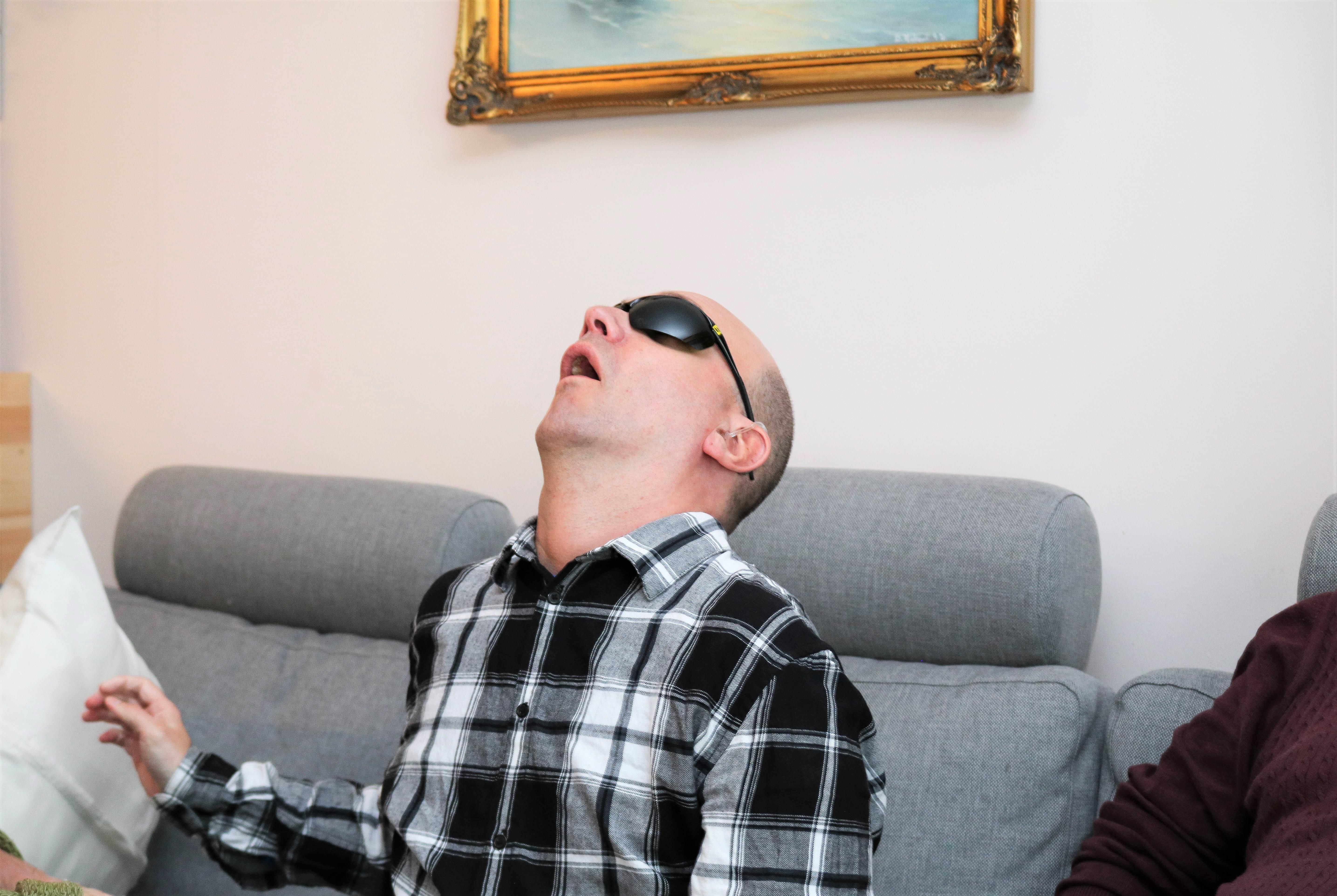 Døvblindmann med mørke briller bøyer seg bakover i en sofa.