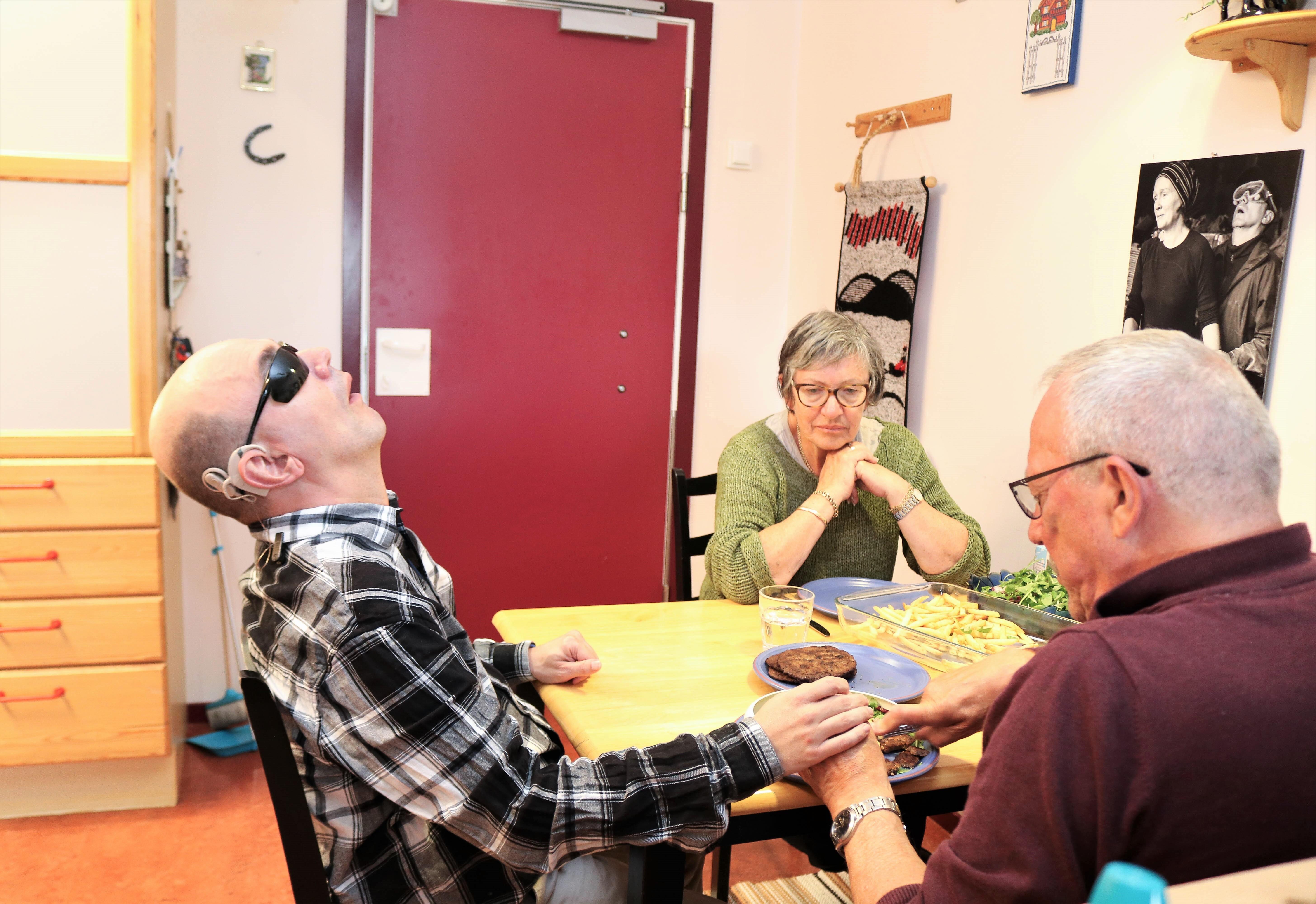 Døvblind mann spiser middag med sine foreldre, far til høyre og mor til venstre.