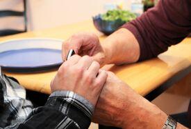 Døvblind mann holder sin høyre hånd over sin fars hender, de kommuniserer via taktilt tegnspråk.