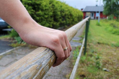 Hånd på et gelender, som går mot et rødt hus.