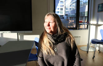 Smilende kvinne i et møterom.