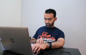 Mann sitter med sin bærbare datamaskin. Han har øynes sine igjen og hendene på tastaturet.