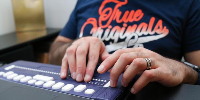 Hender på et punktskrifttastatur som er koblet til en datamaskin.