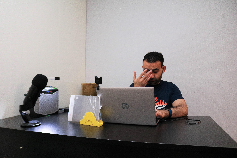 Mann sitter på sin kontorplass og jobber med data. Han holder den ene handa si opp mot ansiktet.