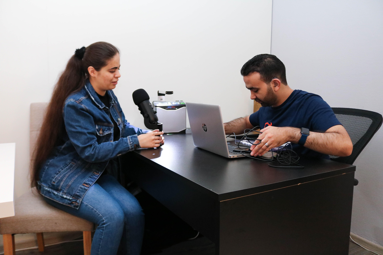 Kvinne og sitter på hver sin side av et bord med diverse podkast-utstyr og en datamaskin.