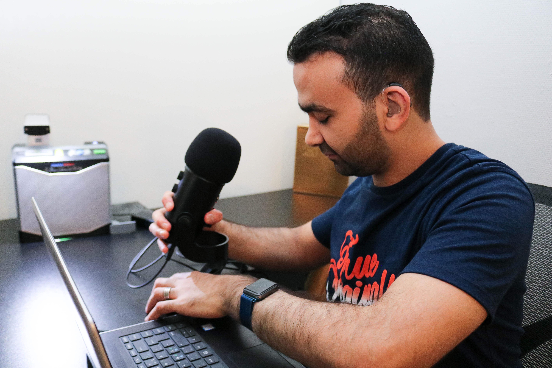 Døvblind mann gjør klar mikrofon for podkast-sending.