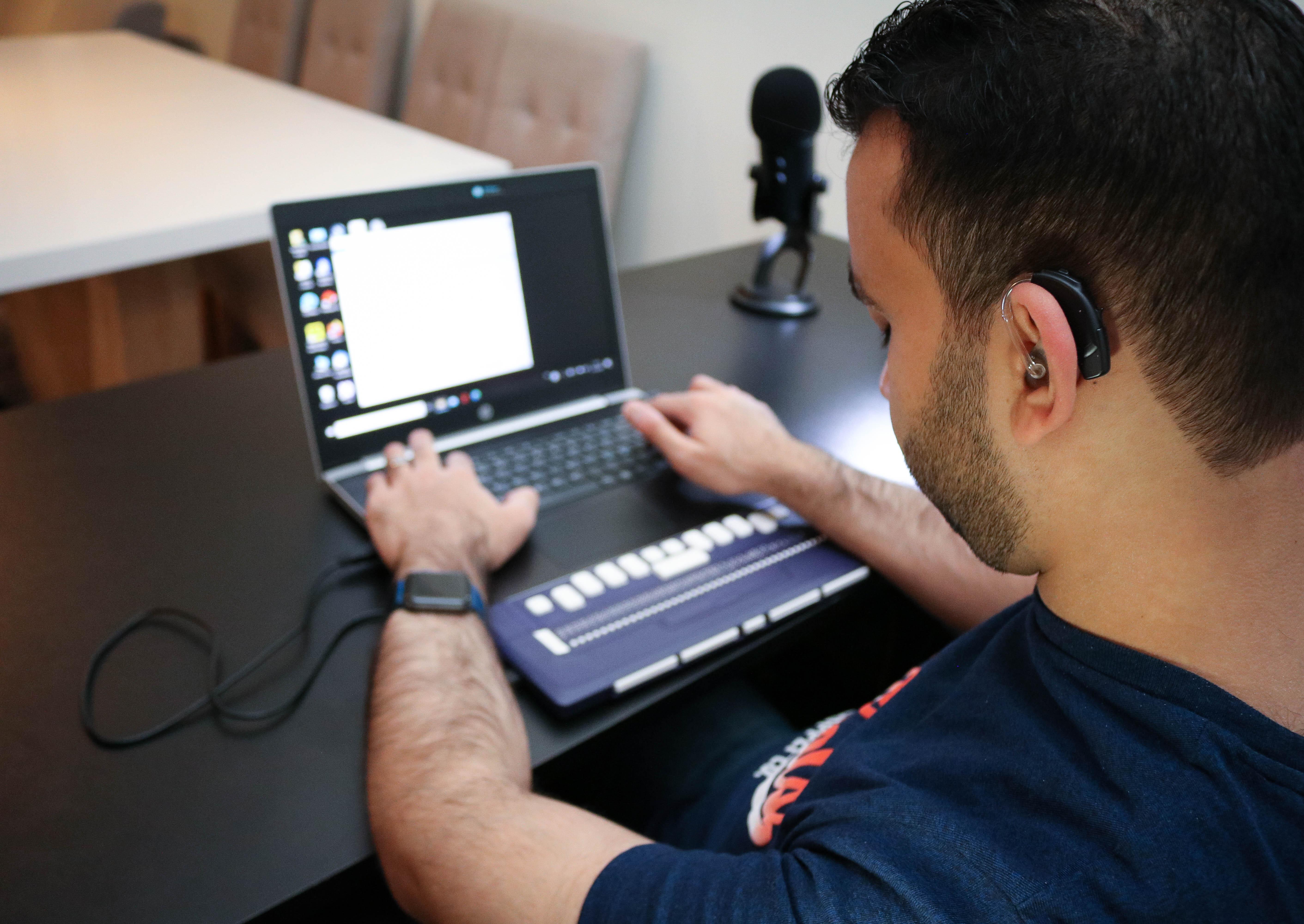 Døvblind mann jobber med sin laptop. Høreapparat på venstre øre er godt synlig.