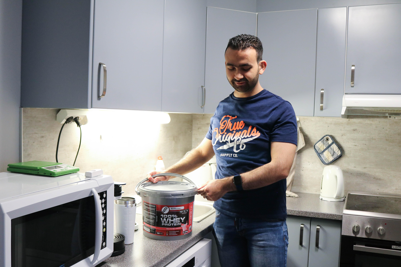 En døvblind mann står på sitt kjøkken med et spann proteinpulver.