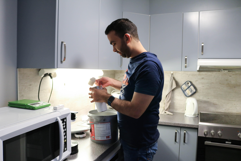 En døvblind mann heller proteinpulver oppi en drikkeflaske. Han er på kjøkkenet sitt.