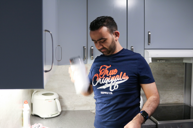 Døvblind mann står på sitt kjøkken og rister en drikkeflaske med proteinpulver.