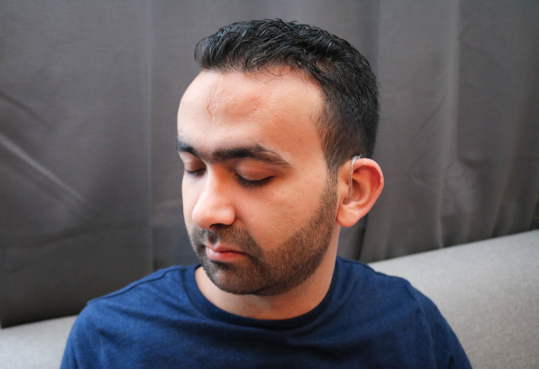 Portrettbilde av døvblind mann. Høreapparat på venstre øre er godt synlig. Breddebilde.