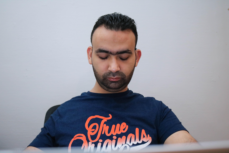Portrettbilde av en døvblind mann som sitter med sin laptop.