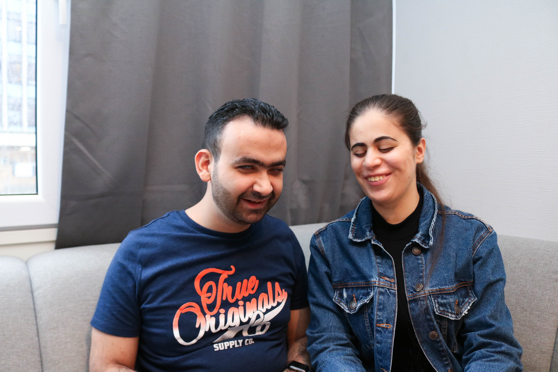 Døvblind mann sammen med sin blinde kone i en grå sofa. De smiler begge to.