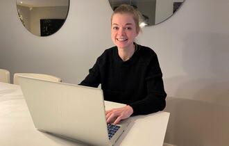 På hjemmekontor, kvinne sitter ved sin sølvgrå laptop. To runde, store speil i bakgrunnen.