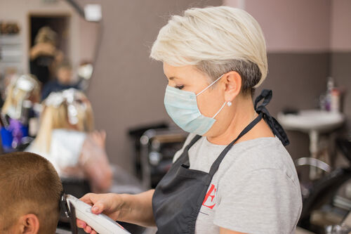 42338596-professional-male-hairdresser-with-face-mask-cut-hair