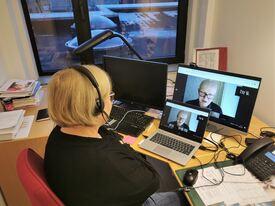Kvinne sitter på kontor og følger webinar på laptop og PC-skjerm samtidig.