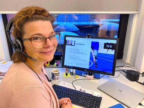 Kvinne med headsett følger med på fagwebinar inne på sitt kontor.