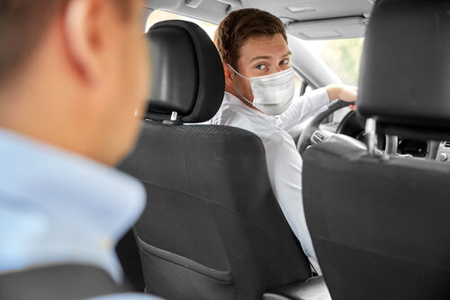 37227399-taxi-driver-in-face-protective-mask-driving-car