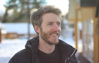 Portrettbilde av smilende mann, vinter-bakgrunn.