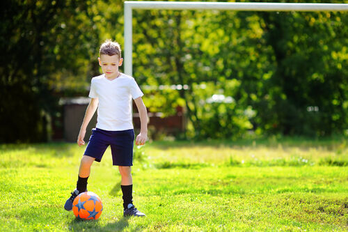 17162881-little-boy-playing-a-soccer-game-on-summer-day