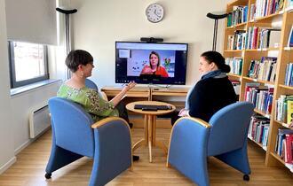 To kvinner sitter på et møterom og følger et webinar på en større tv-skjerm.