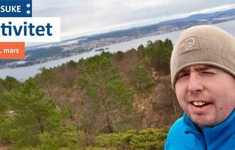 Mann tar selfie i skogsområdet med nedgang til sjøen og noen øyer.
