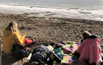 Tre personer med medfødt døvblindhet ligger på en strand, det er vinter og delvis is på sjøen. Solen skinner på stranden.