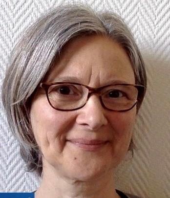 Portrettbilde av kvinne med briller, hun smiler lunt.
