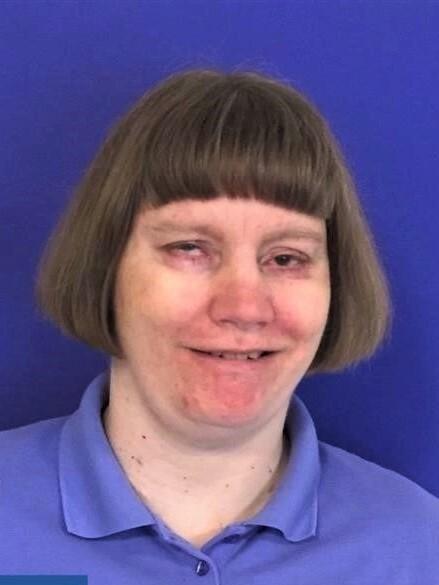 Portrettbilde av døvblind kvinne, mørkeblå bakgrunn.