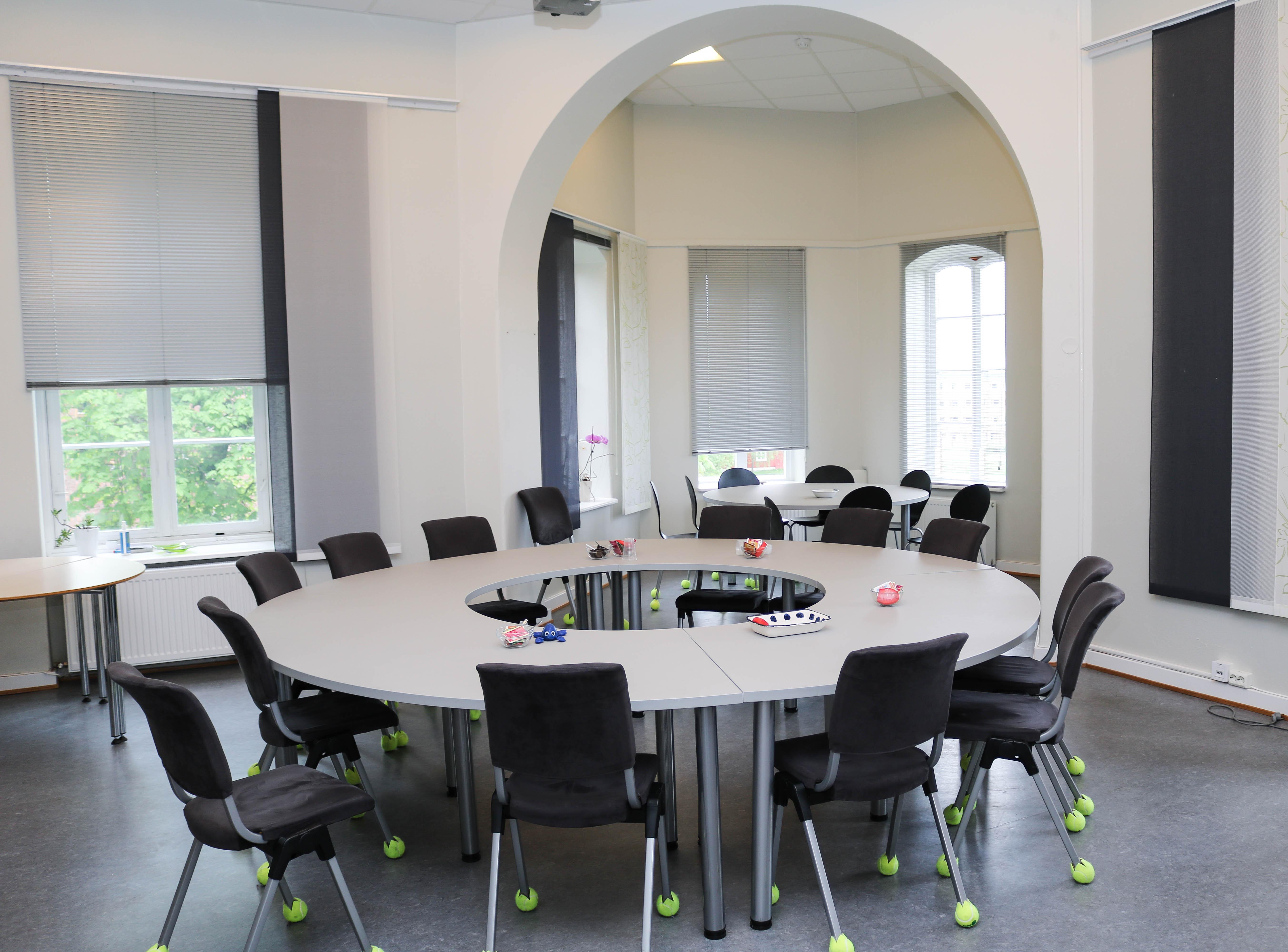 Et rundt bord i et staselig møterom med bue over karnapp. Beina på møtestolene er utstyrt med halve tennisballer for lyddemping mot gulvet.