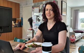 Kvinne på hjemmekontor. Hun sitter på kjøkkenet sitt, spiser salat og jobber samtidig med laptopen sin.