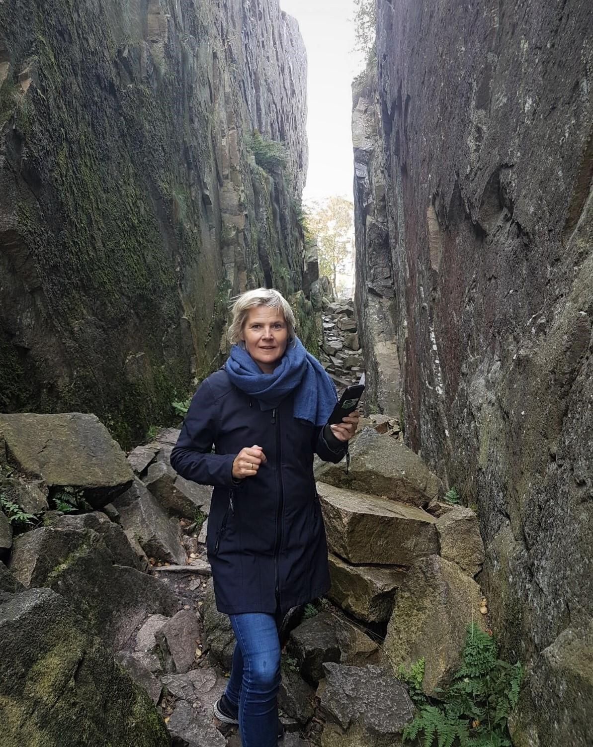 Kvinne står inne i en bergsprekk, det er grønt, grått og vått.