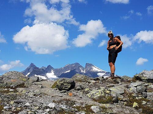 Turkledd kvinne med solbriller i høyt oppe i fjellheimen på sommeren.