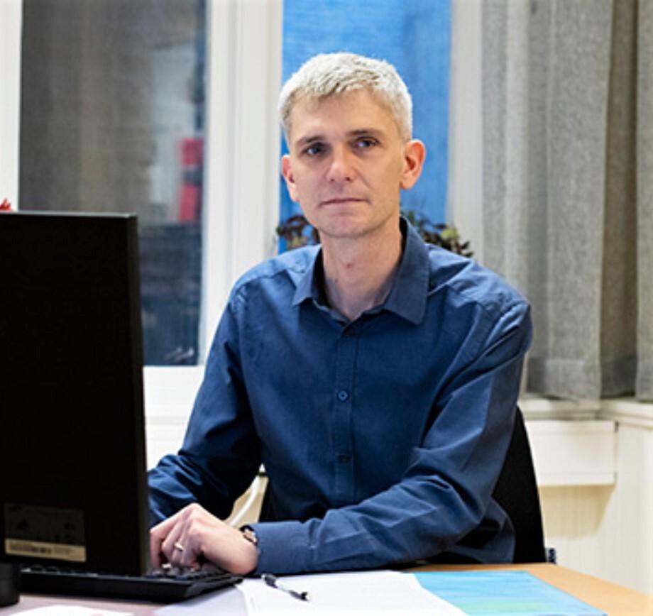 Mann på sitt kontor og ved sin datamaskin.