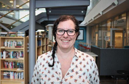 Portrettbilde av en kvinne inne på et kunnskapssenter.