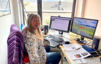 Kvinne på sitt kontor, hun følger med på et fagwebinar via to PC-skjermer.