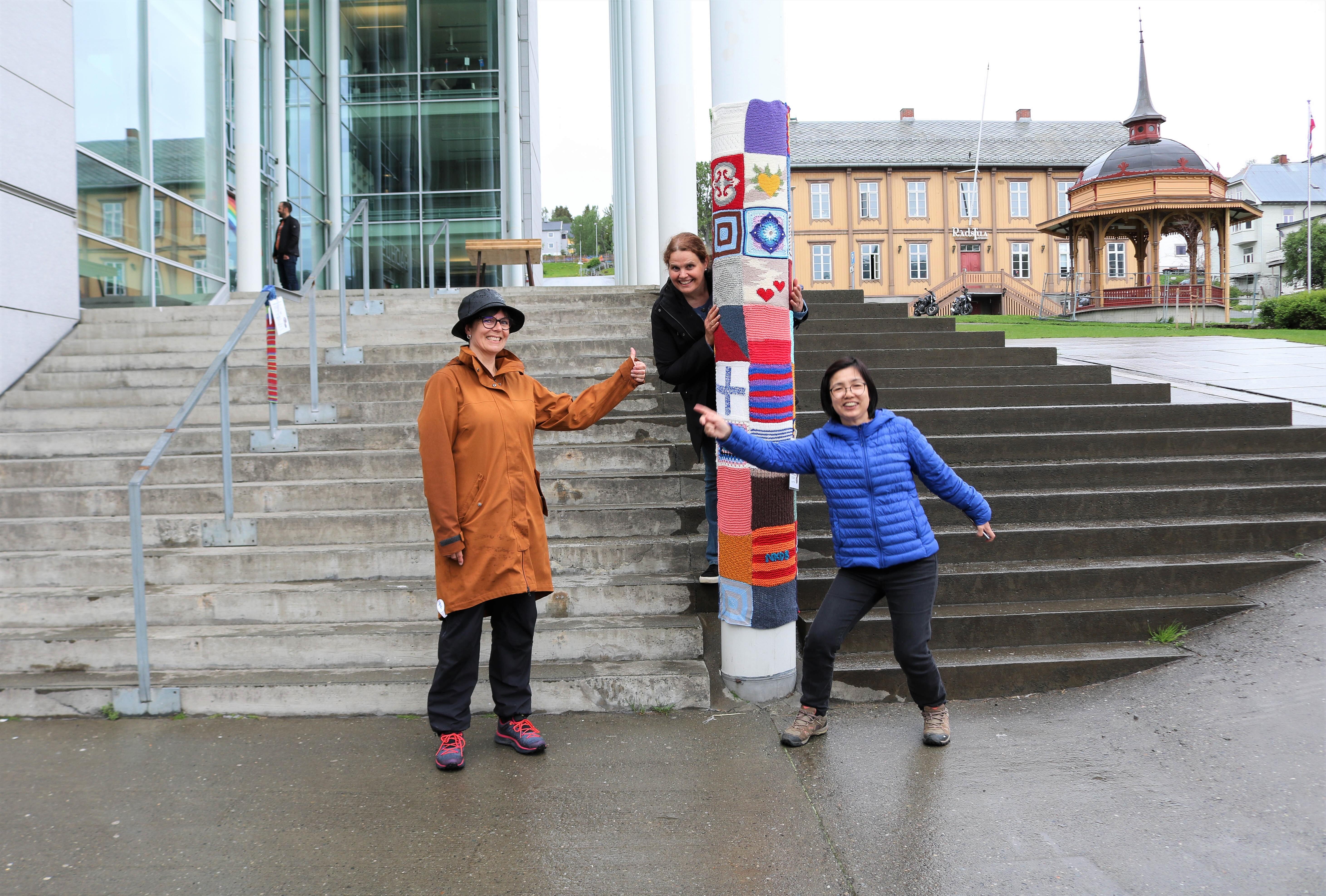 Tre kvinner rundt en søyle med garngraffiti.