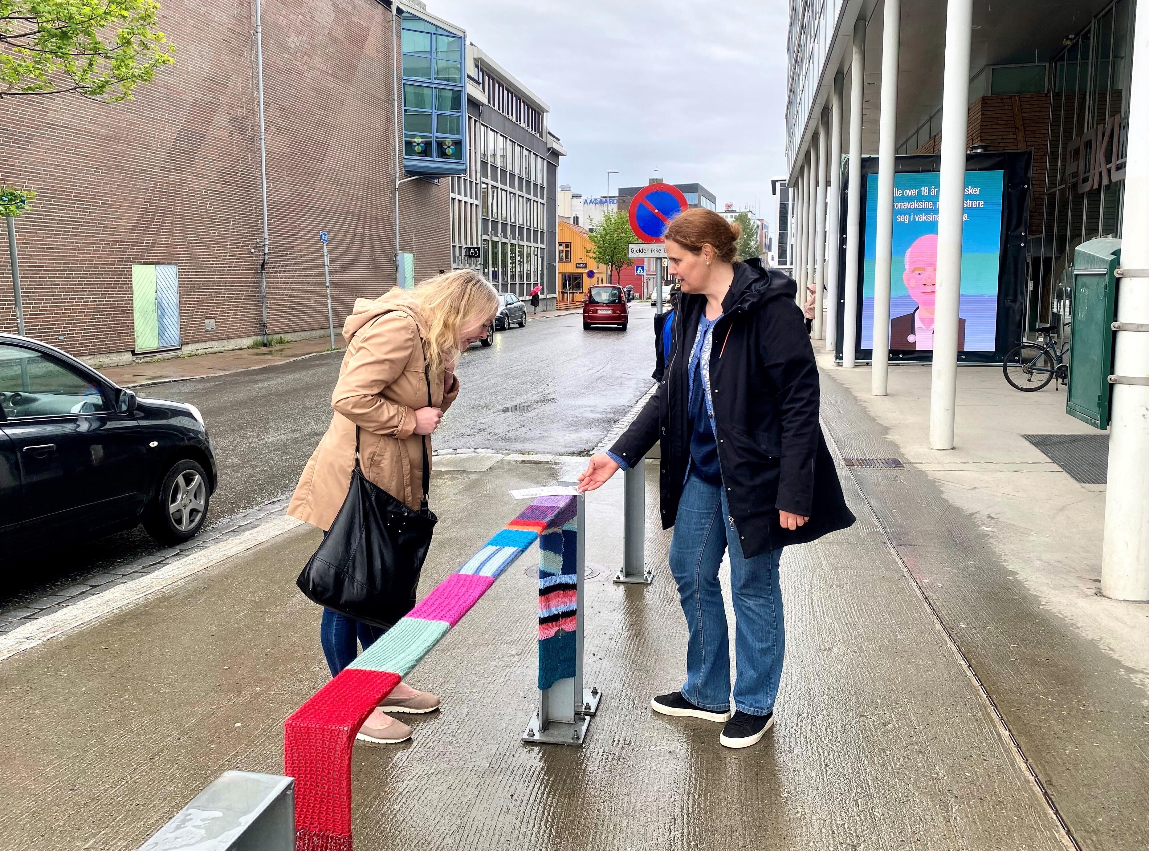 To kvinner samtaler over et rekkverk med garngraffiti.