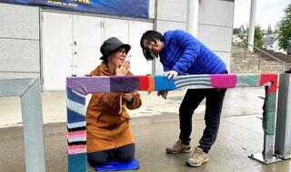 To kvinner jobber med sette i stand garngraffiti på et metallrekkverk.