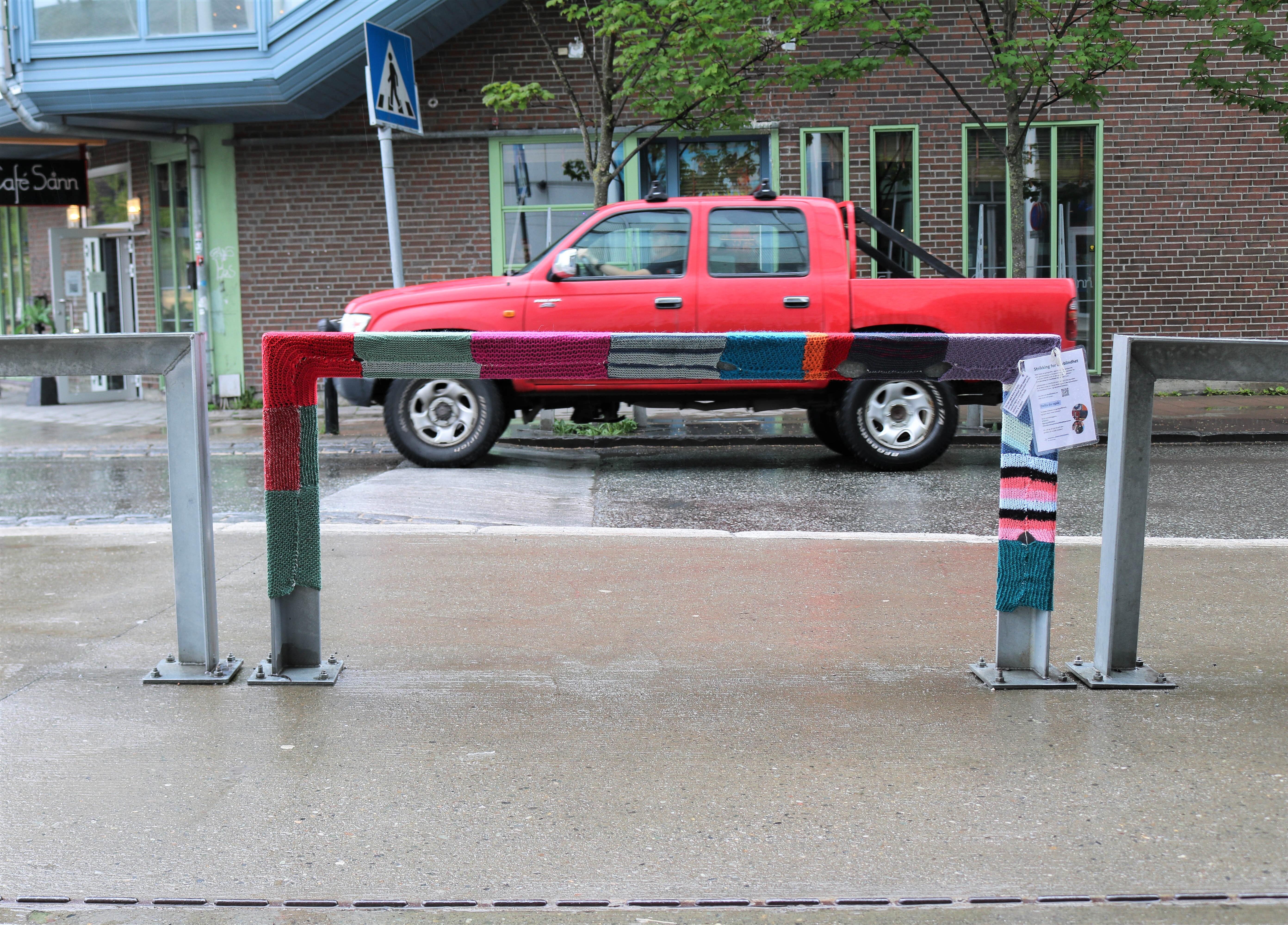 Et metallgelender med garngraffiti, bak kjører en rød pickup.