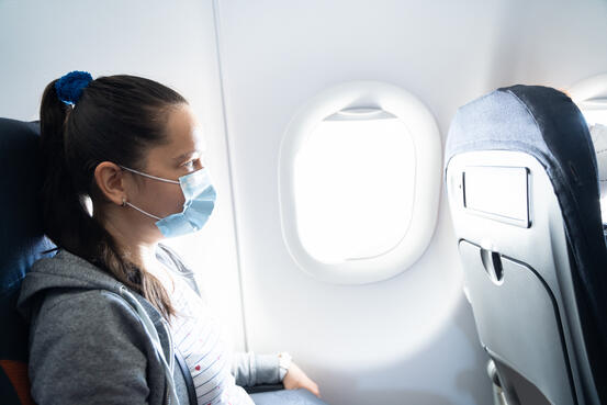47933009-woman-in-face-mask-traveling-on-plane[1]