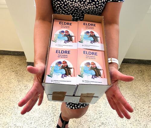 Kvinne holder fram en full eske med brosjyrebøker.