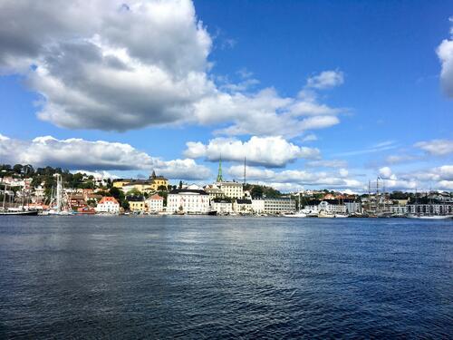 Norsk by sett fra sjøsiden, blå himmel og tykke gråhvite skyer over byen som ligger på Sørlandet.