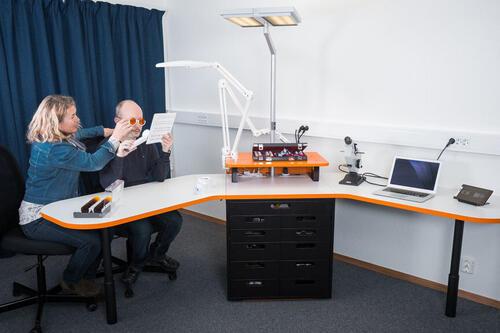 Kvinne og mann tester ut synsfunksjoner med diverse hjelpemidler og apparater.