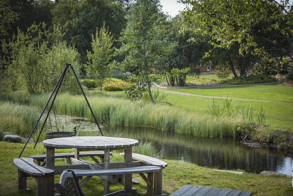 Rasteplass i naturskjønne omgivelser med vann og bålpanne.