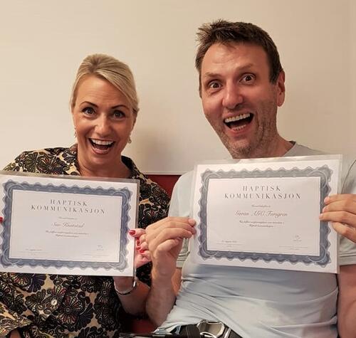 En mann og kvinne stråler om kapp, de holder fram sine sertifiseringsbevis for instruktørkurs i haptisk kommunikasjon.